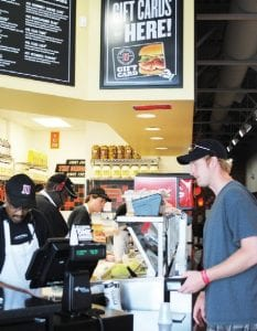 Manager Andre Johnson takes an order from Joshua Carlson of Swartz Creek while PIC Kevin Johnson and Jay Topham make sandwiches behind the counter.