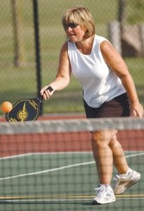 Dana Southwell underhands a return during a recent pickleball game at Elms Road Park in Swartz Creek. Southwell is among about 25 people who gather for the informal sessions of a game only recently introduced to the area.