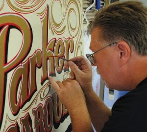 Brian Ashley puts the finishing touches on one of the signs at Crossroads Village. Ashley stands with Chief, one of the well-known horses for the C. W. Parker Carousel. Ashley also is restoring the horses for the carousel, which was built in 1912.