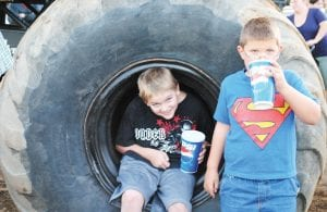 BIG WHEELIN' — Cousins Henry Welch of Flint Twp. and Alex Welch of Burton size up to one of the tires from a monster truck during the Michigan Monster Truck Shoot Out at the Genesee County Fair. The fair wrapped up its annual week of fun Aug. 22.