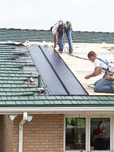 Workers install the solar roofing system on a house. The Freedom Solar Roofing system provides roofs that generate electricity, giving the homeowners the ability to go green and save money.