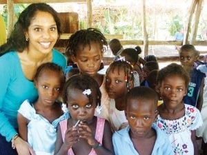 Sumita Joseph, 19, treats patients at a make-shift medical clinic while volunteering in Jacmel, Haiti (left). She spent two weeks in August volunteering, and while there she experienced many things, including visiting children in orphanages (above).