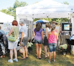 Attendees browse the through paintings at Virginia Maddrell's booth.