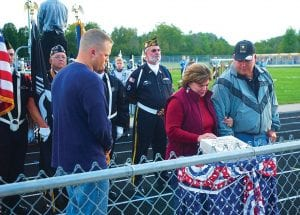 Teri and Dennis Johnson, parents of fallen solider and Carman-Ainsworth student Joe Johnson, stand near a brick memorializing their son during a special tribute at the Sept. 10 Carman-Ainsworth home football game. Johnson, 24, was killed in combat in Afghanistan on June 16.