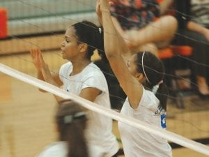 Aarin townsend (left) and Re'Onna Harris defend at the net for the Lady Cavs.