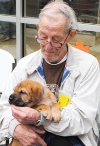 Harold Miller, resident of Prestige Pointe, enjoys some one-on-one time with one of the shelter puppies.