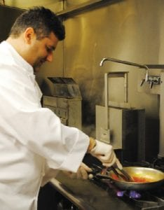 Chef Vito Cangemi, owner of Olio's Cafe & Grill Italian Cuisine, prepares Spaghetti Trapanese, a dish that features a fresh blend of tomatoes, olive oil, basil and garlic tossed with steaming spaghetti.
