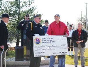 AMVETS Post #3720 Commander Dean Meisegeier, left, hands Rick Henry a $4,000 donation from the post, benefiting the Swartz Creek Area Veterans Memorial.
