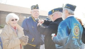 McLeod pins a corsage on Dave Morton, center, a World War II veteran and member of the American Legion Post #294 while Morton's wife, Maryanne, looks on.