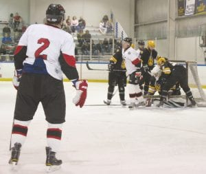 Defenseman Brady Sluman looks on as the Loggers battle with Troy for possession of the puck at the mouth of the net.