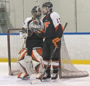 Flushing's Hunter Miller conferred with goalie Casey Bradshaw during a break in the action.