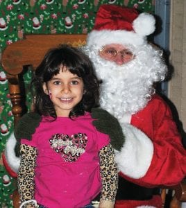 Annessa Atou, 5, sits on Santa's lap during the event.