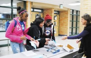 Sixth-grade counselor Theresa Williams, right, helps eighth-graders Deja Lester, Devyn Johnson and Tihirah Ruffin sign in at the event.