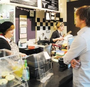 Co-owner Beth Whitman takes an order from customer Tommy Peterson while co-owner Becka Miller prepares a crepe for another customer.