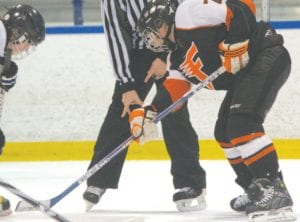 Flushing's Jeff Fisher looked for the puck to drop against an opponent earlier this season.