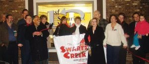 Linda Guigear, branch manager of 1st Securities Mortgage, holding scissors, celebrated the relocation of her business with an official ribbon cutting with the Swartz Creek Area Chamber of Commerce Dec. 7.