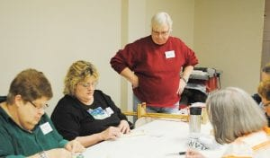 Bev Chapman, center, instructs members of the Genesee Area Bead Society on beading with a loom during a class.