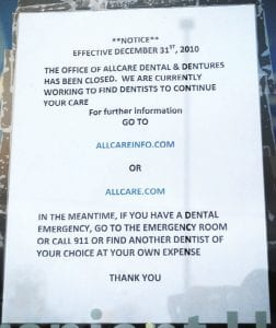 A sign posted outside Allcare Dental & Dentures advises patients to seek alternate help.