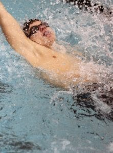 At right, Carman-Ainsworth's Jake Ziaya in a leg of the backstroke race.