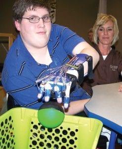 Tim Drost works with Kristine Stefanko of CornerStone Rehabilitation in Davison Township on his SaeboFlex therapy.