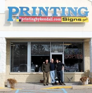 Graphic designer Dee Thomas-Quillen, owner Scot K. Brown and journeyman pressman Sean O'Reilly outside Kendall Printing's new location, 5038 Corunna Rd. At left, O'Reilly operates one of the printing presses.