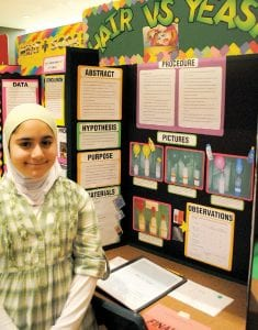 "Fifth-grader Zainab Hafez shows off her science fair project, ""Hair vs. yeast."""