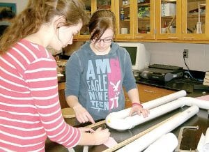 Top, Rachel Sherwin and Kailey Fiewig working on their entries. Left, Sam Lisk and his mousetrap vehicle.