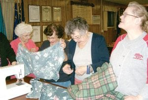 Members work with fabric to make wheelchair bags.