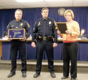 Flint Township Police Chief George Sippert, left, and Township Supervisor Karyn Miller, present Sgt. John Seibel with an award recognizing him for his years of service, March 21.