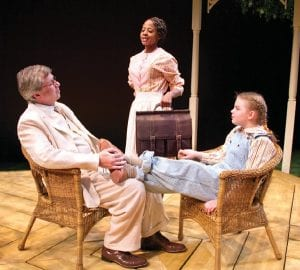 """Left: Associate Artistic Director Walter Hill, left, of Grand Blanc playing Atticus Finch, with resident artist Deirdre S. Baker, Grand Blanc, playing Calpurnia (standing) and student Caroline F. Lostutter of Grand Blanc, playing Jean Louise """"Scout"""" Finch. Above: Caroline, left, playing Jean Louise """"Scout"""" Finch, with student George Lieber of Goodrich, playing Jeremy """"Jem"""" Finch and student Adam Hinde of Flint, seated, playing Charles """"Dill"""" Harris."""