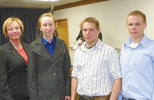 Flint Township Supervisor Karyn Miller stands with recently promoted firefighters Michele Wilson, Jesse Jarnigin and Joshua Jarnigin.