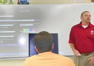 Cory Coombe demonstrates how to draw shapes using an interactive whiteboard and projector.
