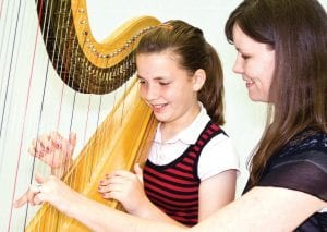 Brittany DeYoung, right, teaching a student on the harp. DeYoung will perform as part of the FSPA Faculty Concert Series with fellow FSPA staff member Meghan Merciers.
