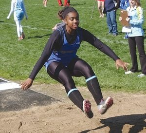 Carman's Devin Willis looks to make a successful landing in the long jump.