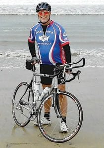 Jay Crane of Essexville is bicycling across America on a 3,457-mile, 33-day trip. He is shown here with his tire touching the Pacific Ocean on the first day of his trip.