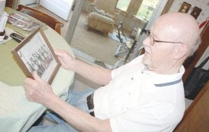 Lloyd Coon of Swartz Creek looks over photos from his days in the U.S. Marines when he was stationed in the Pacific. He will join 39 other area veterans for a trip to Washington D.C. on June 18 to visit the World War II Memorial.