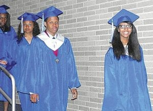 GRADS HONORED — Carman- Ainsworth High School seniors are shown filing into the Honors Convocation in the high school auditorium Tuesday night