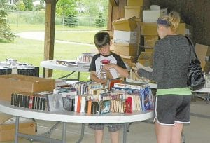 Gavin Dolliver, 8, browsing the tables of books at the GDL McCarty Branch Used Book Sale, June 10.