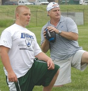 Eric Hipple demonstrates the art of passing to a camper at the Detroit Lions Youth Football Camp at Grand Blanc High.