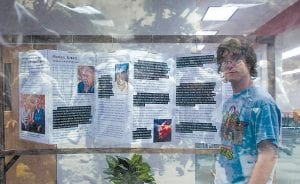 Student Ryan Martin looking back through a transparency at Recounting Memory: Flint-Area Holocaust Survivors & Youth Dialogue with History, a photo exhibit in the lobby of the newly renovated Mott Library, 1401 E. Court St. in Flint.
