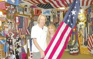 Carol Klee and husband Warren Carter show a feather flag, one of the newest styles on display and for sale at their store for the 4th of July.