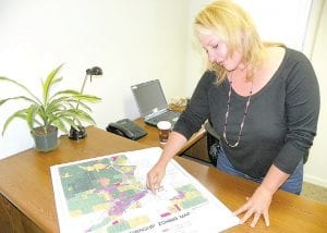 Jane Panessidi in her office at the Michigan Wellness Center with copy of the township zoning map