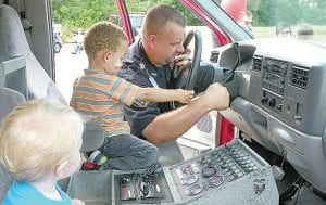 Buddies Emery LaDuke of Flint and Noah Cross of Flint Township, both age 2, get familar with the cab of an ambulance on display at the 28th annual National Night Out. Photo by Rhonda S. Sanders