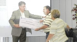 In recogniton of his service as Carman-Ainsworth board president, Superintendent Bill Haley presented a $100 check to Don Conway to support the MEN at WORK father's group that Conway is very active in. Haley said the board figured Conway would appreciate the donation more than a plaque. Conway agreed and thanked the board for