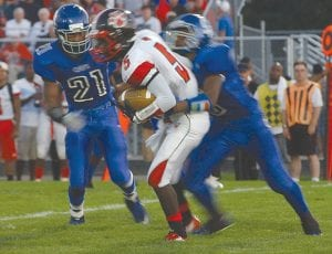 Carman-Ainsworth's Rummeal Branch (21) and Jevonte Alexander (10) close in on Grand Blanc's Jalen Cureton during week one action.