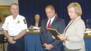 Det. James Santa, center, receives a proclamation regarding his retirement from the Flint Township Police Department from Township Supervisor Karyn Miller while Police Chief George Sippert, left, looks on.