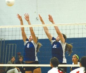 Carman-Ainsworth's Danielle McClung (5), and Jessica McClung (12) team up in recent action.
