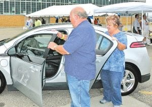 GM worker, and his wife Bonnie get ready to test drive a Chevy Volt during GM's three-day vehicle show at Flint Metal Center on Bristol Road.