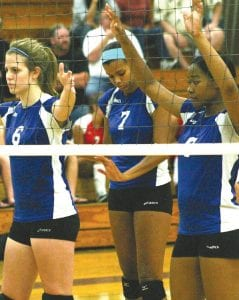 Kristina Dik (#6), Kamrin Gold (#7) and Dena Manns (#8) prepare to handle the net duties for the Carman-Ainsworth varsity volleyball team in recent action.
