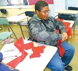 A student works on making flowers for the Carman- Ainsworth sophmore float recently, in preparation for the upcoming Homecoming Game versus Davison High School on Oct. 14. For more about homecoming see page 3.